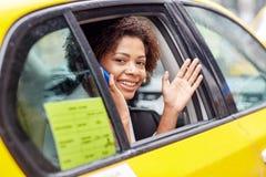 Donna africana felice che rivolge allo smartphone in taxi Fotografia Stock Libera da Diritti
