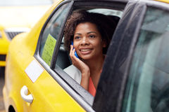 Donna africana felice che rivolge allo smartphone in taxi Immagine Stock Libera da Diritti