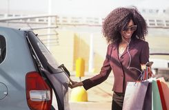 donna africana felice con i sacchetti della spesa che aprono automobile e che mandano un sms sul telefono cellulare Fotografia Stock