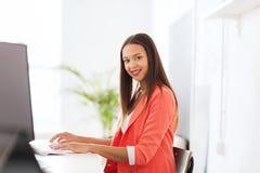 Donna africana felice con il computer all'ufficio immagine stock
