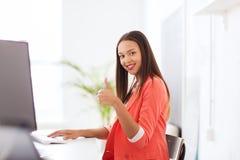 Donna africana felice con il computer all'ufficio immagini stock