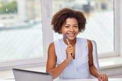 Donna africana felice con il computer portatile all'ufficio Immagine Stock