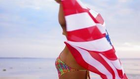 Donna africana felice con la bandiera americana sulla spiaggia archivi video