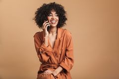 Donna africana graziosa felice che parla lo smartphone e distogliendo lo sguardo immagine stock libera da diritti