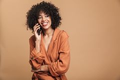 Donna africana graziosa sorridente che parla lo smartphone e distogliendo lo sguardo fotografia stock