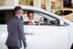 Donna africana sorpresa in macchina nuovo, regalo per la mia bella moglie immagine stock libera da diritti