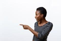 Donna africana sorridente che indica il lato Fotografia Stock