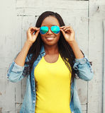 Donna africana sorridente felice in vestiti variopinti ed occhiali da sole Immagini Stock Libere da Diritti