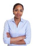 Donna africana sorridente in una camicia blu con le armi attraversate Immagine Stock