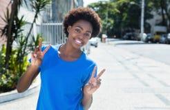 Donna africana in una camicia blu che mostra il segno di vittoria all'aperto in ci Fotografia Stock Libera da Diritti