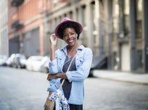 Donna afroamericana alla moda che ascolta la musica sullo streptococco Fotografia Stock Libera da Diritti