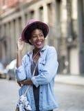 Donna afroamericana alla moda che ascolta la musica sullo streptococco Immagine Stock