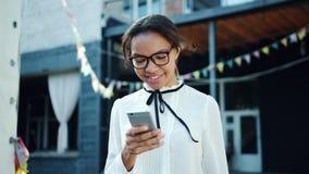 Donna afroamericana allegra che per mezzo dello smartphone all'aperto che sorride archivi video