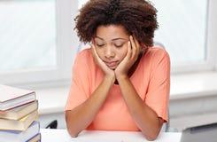 Donna afroamericana annoiata che fa la casa di compito Immagine Stock