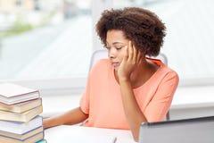 Donna afroamericana annoiata che fa la casa di compito Fotografie Stock Libere da Diritti