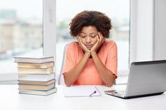 Donna afroamericana annoiata che fa la casa di compito Immagini Stock