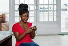 Donna afroamericana attraente che invia messaggio con il telefono fotografia stock