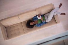 Donna afroamericana a casa con la vista superiore della compressa digitale Fotografia Stock
