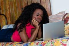 Donna afroamericana che impara online con il computer portatile Fotografia Stock