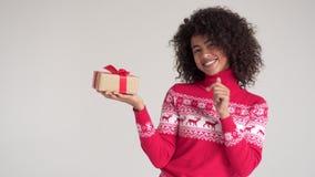 Donna afroamericana che indica al contenitore di regalo di Natale archivi video