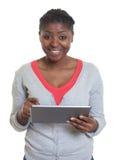 Donna afroamericana che lavora con la compressa Fotografia Stock