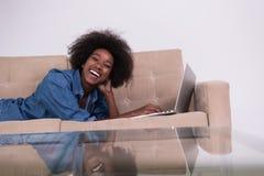 Donna afroamericana che per mezzo del computer portatile sul sofà Fotografie Stock Libere da Diritti