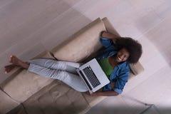 Donna afroamericana che per mezzo del computer portatile sulla vista superiore del sofà Fotografie Stock