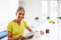 Donna afroamericana che per mezzo della compressa di Digital a casa Fotografia Stock