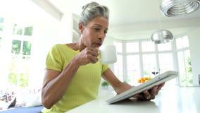 Donna afroamericana che per mezzo della compressa di Digital a casa archivi video
