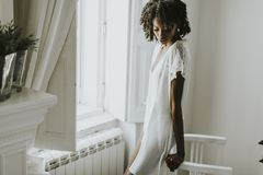 Donna afroamericana che posa nella stanza dalla finestra Fotografia Stock Libera da Diritti