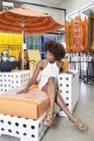 Donna afroamericana che si siede nella sedia del bracciolo al deposito di mobili da giardino fotografia stock