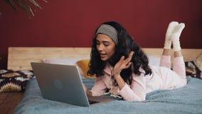 Donna afroamericana che si trova sul letto e che per mezzo del taccuino portatile per la comunicazione di Internet Sta divertendo stock footage