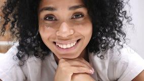 Donna afroamericana che si trova sullo stomaco a letto che sorride, guardando in camera, ridendo stock footage