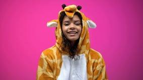 Donna afroamericana che sorride e che esamina macchina fotografica, costume d'uso della giraffa fotografie stock libere da diritti