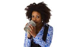 Donna afroamericana con il telefono della latta immagini stock