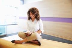 Donna afroamericana con indifferenza vestita che per mezzo della compressa digitale Immagine Stock Libera da Diritti