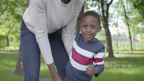 Donna afroamericana del ritratto che fila suo figlio nelle sue armi nella fine verde del parco su, sia ridendo Bambino sveglio stock footage