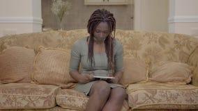 Donna afroamericana del ritratto che si siede nel salone sulla vettura e che cerca qualcosa sulla compressa archivi video