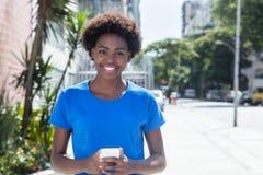 Donna afroamericana di risata in un messaggio di battitura a macchina della camicia blu Fotografie Stock