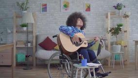 Donna afroamericana disabile con un'acconciatura di afro in una chitarra acustica dei giochi della sedia a rotelle video d archivio