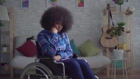 Donna afroamericana disabile triste e sola con un'acconciatura di afro in una sedia a rotelle che si siede da solo stock footage