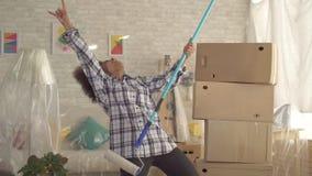 Donna afroamericana felice che balla con il rullo di pittura come il giocatore di chitarra Mo lento video d archivio