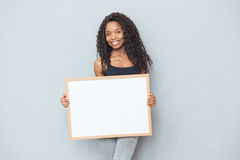 Donna afroamericana felice che mostra bordo in bianco Fotografia Stock Libera da Diritti