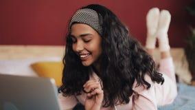 Donna afroamericana felice che si trova sul letto facendo uso del computer portatile per navigare il web Ragazza che indossa sorr archivi video
