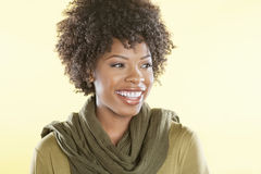 Donna afroamericana felice con una stola rotonda il suo collo che distoglie lo sguardo sopra il fondo colorato immagini stock