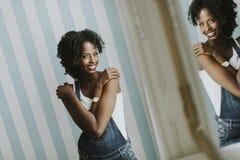 Donna afroamericana graziosa che posa in pantaloni dei jeans Immagine Stock