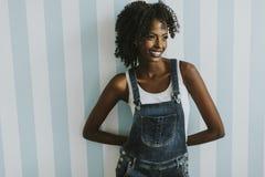 Donna afroamericana graziosa che posa in pantaloni dei jeans Fotografia Stock