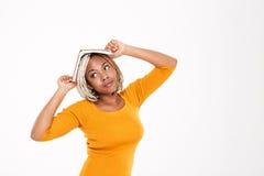 Donna afroamericana pensierosa divertente con il libro sulla sua testa Fotografia Stock