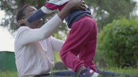Donna afroamericana positiva che abbraccia con il suo piccolo figlio nel parco La madre sparge le sue armi per gli abbracci, il r stock footage