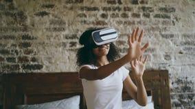 Donna afroamericana riccia che ottiene esperienza facendo uso dei vetri della cuffia avricolare di VR 360 di realtà virtuale a ca stock footage